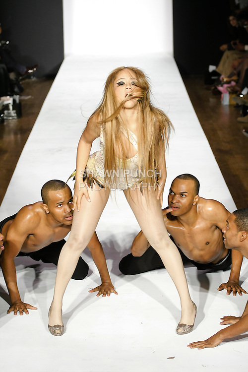 """R&B singer Kat DeLuna performs the world premiere of """"Dancing Tonight"""", in an asymmetrical Swarovski crystalized rayon lycra bodysuit with gold sequined combo and feathers designed by Sachika, at the Sachika Fall 2011 """"The Awakening Of A Swan"""" collection, at the Style 360 Fall 2011 fashion show, during New York Fashion Week."""