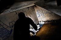"""A prison guard searches for drugs, weapons and other banned items in a Mara gang members cell during a random cell search at the detention center in San Salvador, El Salvador, 20 February 2014. Although the country's two major gangs reached a truce in 2012, the police holding cells currently house more than 3000 inmates, five times more than the official built capacity. Partly because the ordinary Mara gang members did not break with their criminal activities (extortion, street-level distribution of drugs, etc.), partly because Salvadorean police still applies controversial anti-gang law which allows to detain almost anyone for """"suspicion of gang membership"""". Accused young men are held in police detention centers where up to 25 inmates may share a cell of five-by-five metres. Here, in the dark overcrowded cages, under harsh and life-threatening conditions, suspected gang members wait long months, sometimes years, for trial or for to be transported to a regular prison."""