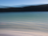 A long exposure blur of the colorful waters, shoreline and mountains at Laguna Amarga.