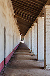 Covered outdoor walkway with adobe and stucco walls and columns,clay floor and open beams at Mission La Purisima State Historic Park, Lompoc, California.  Mission La Purisima, founded in 1787 by Franciscan Padre Presidente Fermin Francisco Lasuen. La Purisima was the eleventh mission of the twenty-one Spanish Missions established in what later became the state of California.