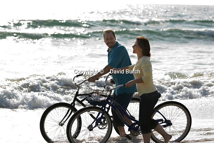 Mature couple walking with bicycles at seashore, smiling