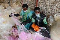 RWANDA, Kigali, plastic recycling at company ecoplastics, worker sort used plastic foils before processing to granulate which is used for new plastic products / RUANDA, Kigali, plastic recycling bei Firma Ecoplastics, Plastikmuell, Sortierung alte Folien