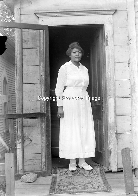 """WOMAN IN WHITE<br /> The screen door is propped open with a rock, and a rug has been pulled across the threshold, transforming a simple doorway into a contrasting dark frame for a portrait of a woman in gleaming white. Like most of the photographs in the collection the attention to detail, the composition and the knowledge of shadow and light show a craftsman at work. This photograph is """"made"""" rather than """"taken"""".<br /> <br /> Photographs taken on black and white glass negatives by African American photographer(s) John Johnson and Earl McWilliams from 1910 to 1925 in Lincoln, Nebraska. Douglas Keister has 280 5x7 glass negatives taken by these photographers. Larger scans available on request."""