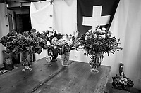 Switzerland. Canton Ticino. The family Cereghetti runs the Agriturismo Dosso dell'Ora on Monte Generoso. They celebrated a few days before the fiftieth anniversary of Marina Cereghetti. Flowers on the table and swiss flag on the wall. The flag of Switzerland displays a white cross in the centre of a square red field. The white cross is known as the Swiss cross. A plaster statue of the Virgin Mary stands on the ground in a floral decoration. 23.06.2020 © 2020 Didier Ruef