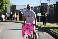 Max Perez rides his bike as he holds a sign, Friday, May 29, 2020 during a protest caravan and rally at the Tyson Foods plant at 600 Berry St. in Springdale. A poultry workers' rights group, Venceremos, hosted a rally and car caravan to protest how workers are being treated in relation to covid-19. Check out nwaonline.com/200530Daily/ for today's photo gallery. <br /> (NWA Democrat-Gazette/Charlie Kaijo)