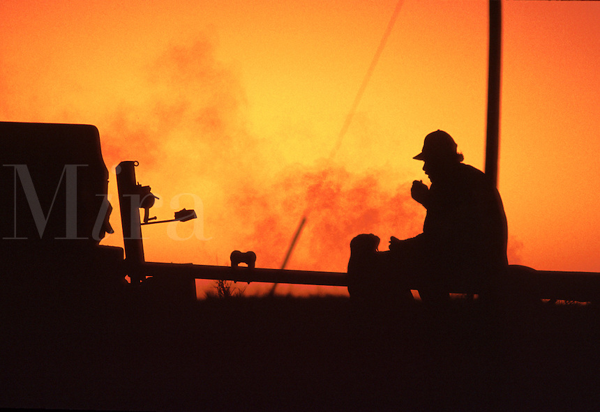 Silhouette of a man sitting on a boat trailer hitch at dawn.