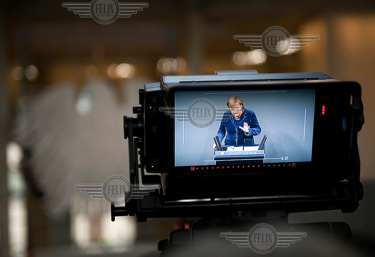 German Chancellor, Angela Merkel, viewed on the monitor screen of a video camera as she talks during a debate about the Euro crisis in the Parliament Chamber at the Reichstag.
