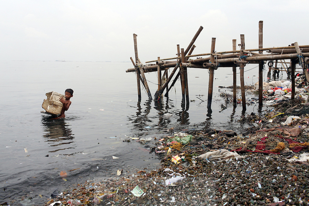 """An Indonesian boy plays with a polystyrene box in the bay of Jakarta. According to the the Climate Reality Project, """"without flood protection measures, sea level rise could expose up to 6 million Indonesians to annual coastal flooding. The worst of the flooding would occur on the island of Java, where Jakarta is located."""""""