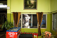 Thailand. Bangkok. Restaurant in Tha Tian. Green walls, brown curtains, a clock, a painting with elephants, fire extinguishers on the flloor, a Wall's ice cream freezer (Wall's (Ice Cream) Ltd is the name of the company that for many years, as an independent and then as a Unilever subsidiary, made and marketed the Wall's brands, such as Magnum, Carte d'Or,..), a religious altar with flowers and electric lights. Through an open window, view on an alley with coolies and shophouses, providing business in wholesale and retail sectors. Tha Tian is a community located in the downtown area and in the center of the urban historic district, called Koh Rattanakosin. 30.03.09 © 2009 Didier Ruef