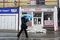 Pictured: A woman with an umbrella walks in front of closed shops that were affected by the floods in Taff Street, Pontypridd. Wednesday 04 March 2020<br /> Re: Revisiting the flood affected areas in Pontypridd, Wales, UK.