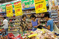 Chinese  consumers check packed food in Wumart supermarket in Beijing, China. China's inflation rate last month soared to its highest level in more than a decade, official data showed Monday, sounding new alarm bells that will likely lead to further monetary tightening..13 Aug 2007