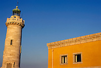 Lighthouse and yellow building at the entrance of the port, Marseille, France.