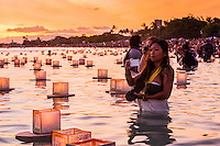 On Memorial Day at sunset, Asian woman photographs lanterns floating in the water during the 15th Annual Lantern Floating Ceremony at Ala Moana Beach Park, Honolulu, O'ahu.