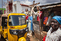 """Nigeria. Enugu State. Enugu. Town center. A smiling elderly Igbo woman stands close to a yellow auto rickshaw used by """"Keke"""" drivers for transporting people around town. The tricycle better known in Nigeria as the Keke NAPEP is gaining the dominance on Nigerian roads sweeping every street of cities and villages. The auto rickshaw is a common form of urban transport, both as a vehicle for hire and for private use. The old woman is wearing a head tie which is a women's cloth head scarf. The head tie is used as an ornamental head covering or fashion accessory, or for functionality in different settings. Its use or meaning can vary depending on the country and/or religion of those who wear it. The head tie is called gele in Nigeria. Catholic religious symbols. Plaster statues of the crucifixion of Jesus, Jesus Blessing and the Virgin Mary. Collectively referred to as the Passion, Jesus' suffering and redemptive death by crucifixion are the central aspects of Christian theology concerning the doctrines of salvation and atonement. Enugu is the capital of Enugu State, located in southeastern Nigeria.  28.06.19 © 2019 Didier Ruef"""