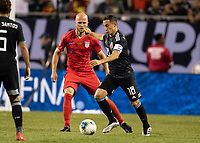 CHICAGO, IL - JULY 7: Michael Bradley #4 defends against Andres Guardado #18 during a game between Mexico and USMNT at Soldiers Field on July 7, 2019 in Chicago, Illinois.