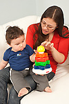 7 month old baby boy interaction with mother, interested as she demonstrates new toy