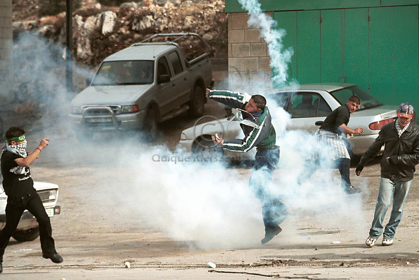 A Palestinian runs with a tear gas canister fired by Israeli troops as he clears it away from the crowd during clashes 25 October 2000, in Ramalah.