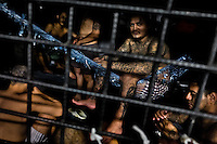 """A member of the 18th Street gang (M-18) sits in a homemade hammock in a cell at the detention center in San Salvador, El Salvador, 20 February 2014. Although the country's two major gangs reached a truce in 2012, the police holding cells currently house more than 3000 inmates, five times more than the official built capacity. Partly because the ordinary Mara gang members did not break with their criminal activities (extortion, street-level distribution of drugs, etc.), partly because Salvadorean police still applies controversial anti-gang law which allows to detain almost anyone for """"suspicion of gang membership"""". Accused young men are held in police detention centers where up to 25 inmates may share a cell of five-by-five metres. Here, in the dark overcrowded cages, under harsh and life-threatening conditions, suspected gang members wait long months, sometimes years, for trial or for to be transported to a regular prison."""