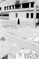 """Iraq. Baghdad. Iraqi Intelligence Service building """"Al Mokhbrat"""". A woman, dressed with a black veil covering her entire body, walks near the main entrance of the building which was heavily hit by air strikes attacks (missiles) from the coalition forces (american and english army), then looted and burned by thieves, called Ali Baba. A frame with a picture of Saddam Hussein as head of state has been thrown on the ground. © 2003 Didier Ruef"""