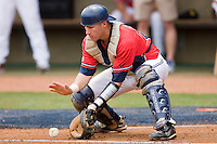 Catcher Miles Hamblin #24 of the Ole Miss Rebels fields a throw at home plate against the St. John's Red Storm at the Charlottesville Regional of the 2010 College World Series at Davenport Field on June 6, 2010, in Charlottesville, Virginia.  The Red Storm defeated the Rebels 20-16.  Photo by Brian Westerholt / Four Seam Images
