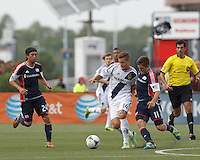 LA Galaxy substitute midfielder Robbie Rogers (14) brings the ball forward as New England Revolution substitute midfielder Kelyn Rowe (11) does yellow card defense. In a Major League Soccer (MLS) match, the New England Revolution (blue) defeated LA Galaxy (white), 5-0, at Gillette Stadium on June 2, 2013.