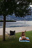 Switzerland. Canton Ticino. Tenero. Camping Campofelice. A man is lying on the grass near the sandy beach on the Lago Maggiore's shores. The beach is perfect to play, relax or sunbathe. Lake Maggiore (Lago Maggiore) or Lago Verbàno is the largest lake in southern Switzerland. 20.07.2018 © 2018 Didier Ruef