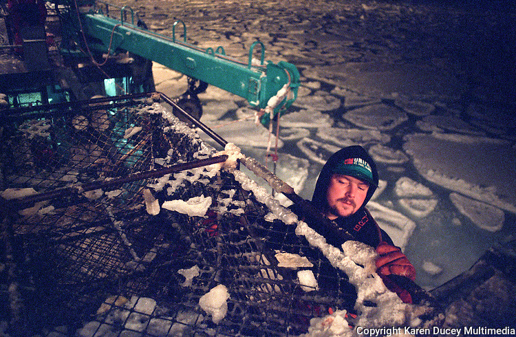 """Crewmen Larry Murphy climbs along the side of """"the stack"""" on the fishing vessel """"Kiska Sea"""" as it fishes for opilio crab in the arctic ice floes of the Bering Sea in January and February of 1995.  With pancake ice below death by hypothermia would be certain were he to fall overboard.  Crab pots weighing approximately 700 pounds are stacked one on top of the other.  During the 1990's the pot limit was 250 pots for larger vessels such as this one.  The Bering Sea is known for having the worst storms in the world.  Nights are long and cold in the arctic in the winter.  Crab fishing in the Bering Sea is considered to be one of the most dangerous jobs in the world.  This fishery is managed by the Alaska Department of Fish and Game and is a sustainable fishery.  The Discovery Channel produced a TV series called """"The Deadliest Catch"""" which popularized this fishery."""