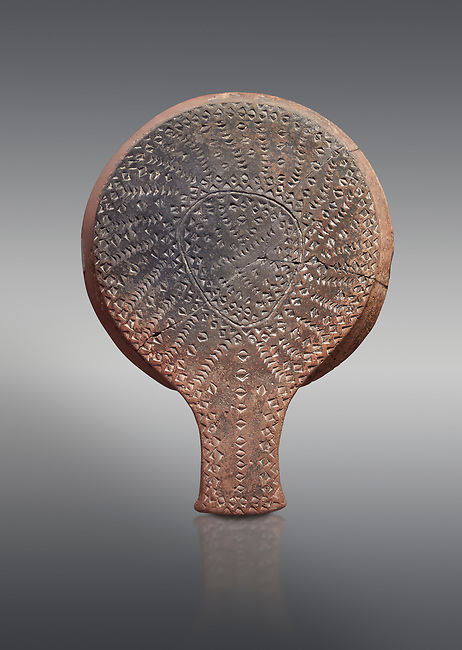 Cycladic terracotta 'frying pan' with incied linear decoration from Chalandriani, Syros. Early Cycladic period II 2800-2300 BC), National Archaeological Museum Athens, Cat No 5012.  Grey background.<br /> <br /> <br /> These so called 'frying pans' wre created by the Keros-Syros culture and are their useage is uncertain. The compex geometric patterns on their bases suggest that they may have had some symbolic meaning and were used in religious of magical rituals. They could also have served practical purposes being used as dishes, mirror mounts, astrolabes or metris measured for salt traders.