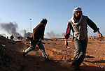 Opposition rebels flee an attack by Qaddafi forces near an oil refinery in Ras Lanuf, Libya, March, 11, 2011. Loyalist forces of Col. Muammar Qaddafi pushed rebels back from the strategic oil town with air strikes, artillery and small arms fire.