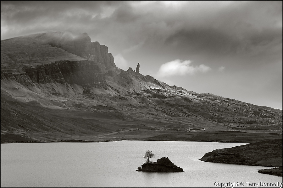 Isle of Skye, Scotland:<br /> Old Man of Storr & peaks of the Totternish ridge tower over lake Fada in a clearing storm