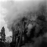 """Edifice commercial et de bureaux, magasin """"Au gaspillage"""" au début du XXe siècle, """"Au bon marché de Paris, """"le Printemps"""" et les assurances """"Le continent"""" dans les années 1960, """"Bouchara"""", """"Zara"""", 47 rue d'Alsace-Lorraine. 11 Mars 1964.Vue de l'incendie de l'immeuble du Printemps et l'intervention des pompiers ; trois pompiers sur la grande échelle dont deux au niveau du dernier étage dirigeant le jet de la lance d'incendie vers le troisième étage, dans des nuages de fumée épaisse."""