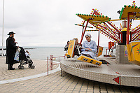 An Hasidic man minds his baby as he watches his wife and child swing round on a seaside ride in Aberystwyth. .