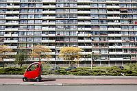 Nederland Zaandam 2017 04 22 . Oudere man rijdt  in een overdekte scootmobiel langs een flat. Foto Berlinda van Dam / Hollandse Hoogte