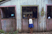 Rio Branco, Brazil. Girl at the window of a wooden shack.