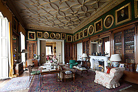 A grand, Vitorian library with gilded plasterwork ceiling and enclosed antique bookcases