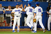 Florida Gators Nelson Maldonado (27) high fives Keenan Bell (32) and Jordan Butler (15) during a game against the Siena Saints on February 16, 2018 at Alfred A. McKethan Stadium in Gainesville, Florida.  Florida defeated Siena 7-1.  (Mike Janes/Four Seam Images)