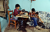 January 1979, La Paz, Bolivia. In Bolivia, these children are employed in a workshop to produce clothing. | Location: La Paz, Bolivia.  Child labor as seen around the world between 1979 and 1980 - Photographer Jean Pierre Laffont, touched by the suffering of child workers, chronicled their plight in 12 countries over the course of one year.  Laffont was awarded The World Press Award and Madeline Ross Award among many others for his work.