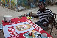 Stone Town, Zanzibar, Tanzania.  Painter Oscar Mwingira makes a banner for an upcoming sporting event.