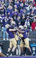 The Huskies celebrate Chico McClatcher's first quarter touchdown.