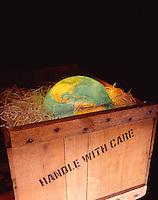 Glowing globe in shipping crate.
