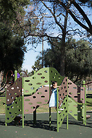 A girl climbs a climbing play structure above a rubberized mat at South Gate Park.