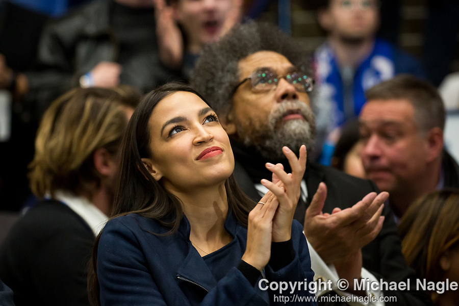 Congresswoman Alexandria Ocasio-Cortez, center, and Cornel West, philosopher and activist,  right of center, listen to U.S. Senator and Democratic Presidential Candidate Bernie Sanders during a rally ahead of the New Hampshire primary election at the University of New Hampshire on Monday, February 10, 2020 in Durham, New Hampshire. Photograph by Michael Nagle/Redux Pictures