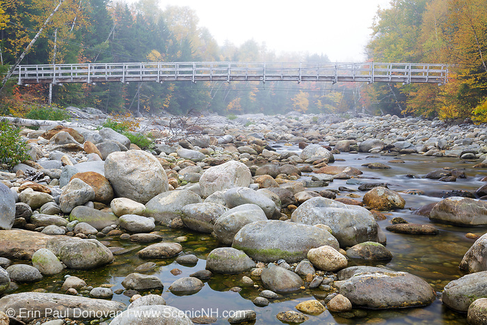 Suspension foot bridge, which crosses the Peabody River at the start of the Great Gulf Trail in Green's Grant of the New Hampshire White Mountains on a foggy autumn morning.