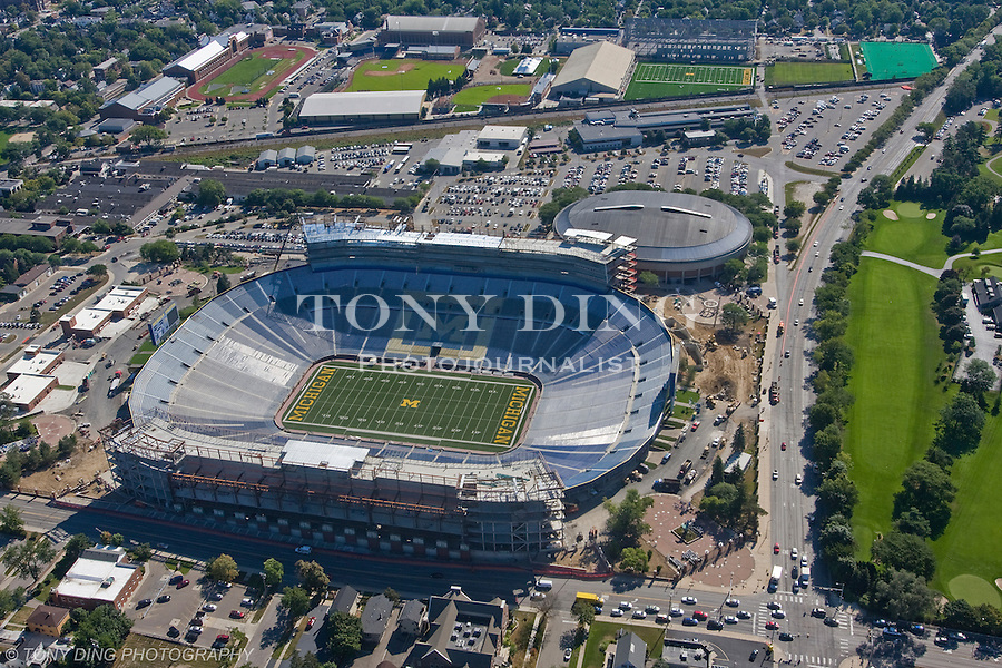 """15 August 2008: Aerial view of Michigan Stadium undergoing major renovations and expansion in Ann Arbor, MI. The three year, $226 million project will add 82 luxury suites, a new press box, improved stadium seating and concourse fans amenities, as well as premium club seating sections that will eventually bring the """"Big House"""" capacity to over 108,000. Project completion is scheduled for August 2010. Adjacent to the stadium is Crisler Arena, Michigan's basketball venue."""