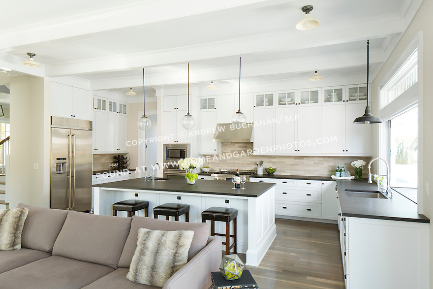Shaker-style white cabinetry and dark stone countertops in an open and airy kitchen.