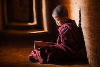 Young monk reading in a temple in Bagan, Myanmar