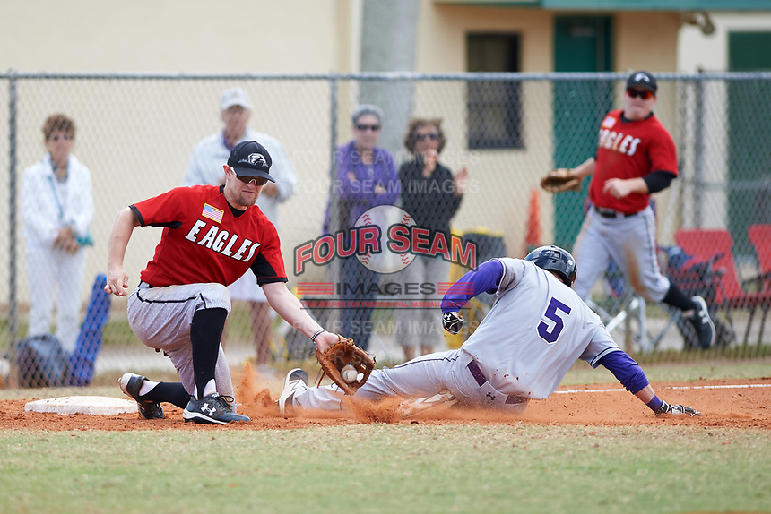 Edgewood College Eagles Tim Nunn (12) fields a throw as Adrian Spitz (5) slides into third base during a game against the New York University Violets on March 14, 2017 at Terry Park in Fort Myers, Florida.  NYU defeated Edgewood 12-7.  (Mike Janes/Four Seam Images)