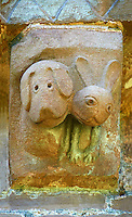 Norman Romanesque exterior corbel no 33  -  sculpture of.very modern cartoon like hound and a hare. In the Bestiary dogs are like preachers who put men back on the right course of righteousness and the hare represents men who fear God and put their trust in the creator . The Norman Romanesque Church of St Mary and St David, Kilpeck Herefordshire, England. Built around 1140