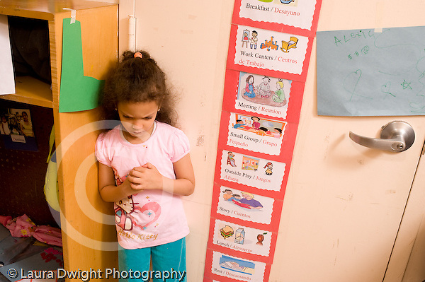 Preschool ages 3-5 separation start of day sad girl standing by cubbies horizontal