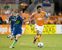 Seattle Sounders midfielder Osvaldo Alonso (6) grabs hold of Houston Dynamo forward Brian Ching (25).  Houston Dynamo tied Seattle Sounders 1-1 on August 23, 2009 at Robertson Stadium in Houston, TX.